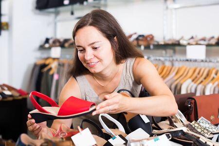 신발장에서 신발을 선택하는 매력적인 여성 고객의 초상화