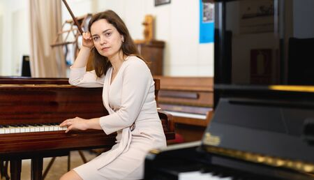 Young woman buys pianoforte in a music store