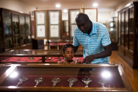 Afro father and his daughter looking at exhibits in glass stands at historical museum