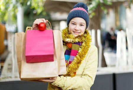 Porträt eines jugendlichen Mädchens, das mit Taschen auf dem Weihnachtsmarkt glücklich aussieht?