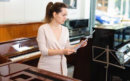 Pretty woman seller in piano music store