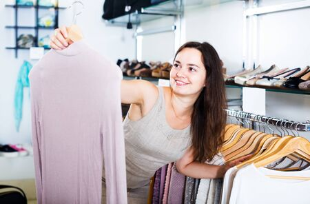 Smiling brunette girl selecting basic blouse in apparel store Banque d'images