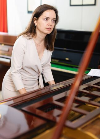 Young woman buys a piano in a music store 写真素材