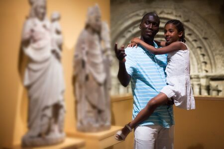 African American man and his daughter visiting exposition of museum with exhibits of medieval art Stock Photo