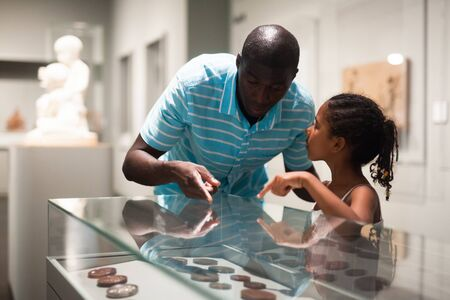 African American father and daughter looking at stands with exhibits at historical museum Imagens