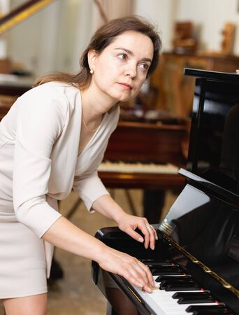 Beautiful girl chooses a piano in a music store
