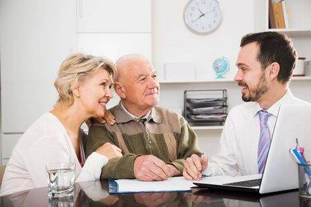 Old man and mature woman consult with social department employee in social service