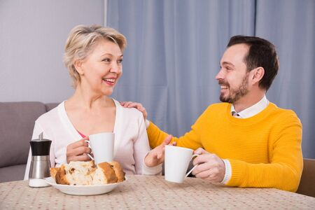 Smiling mature mother and son having breakfast and warmly talk at table at home