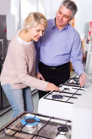Smiling mature couple are buying in center of household appliances the plate with oven for house.
