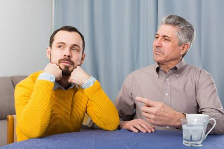 Mature father and his son are serious conversation at home and solve problems Imagens