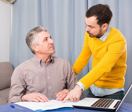 Adult father and son discuss difficult and serious contract at home