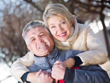 Mature couple walking along coastal park at sunny day. Focus on both persons Banco de Imagens