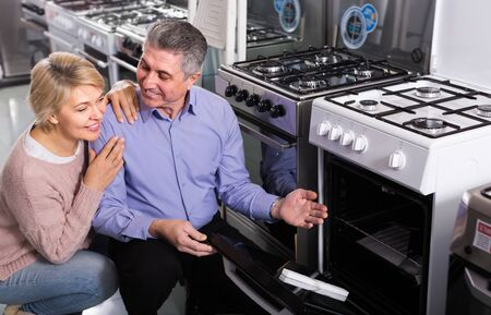 Husband and wife in store of household appliances select to themselves gas stove Stock Photo
