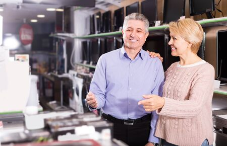 Mature married couple are happy to see variety of household appliances in shop Stock Photo