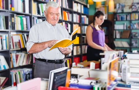 Male 61-67 years old is choosing book for reading in free time in bookstore.