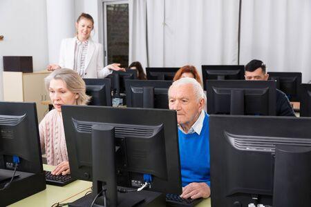 Computerunterricht für Erwachsene. Gruppe von Senioren, die lernen, Computer mit einer jungen Tutorin im Klassenzimmer zu benutzen Standard-Bild