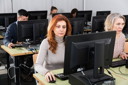 Portrait of focused mature woman during computer classes at university of third age