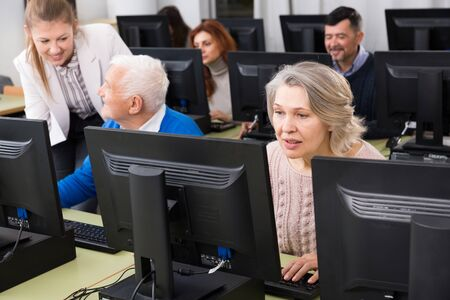 Portrait of mature people studying together with young female coach in university computer class