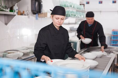 Portrait of young woman sorting and arranging clean dishware at restaurant kitchen