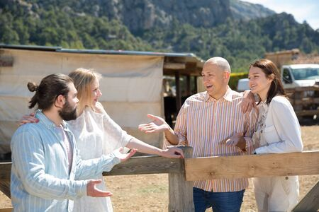 Happy friends chatting on rustic farm background