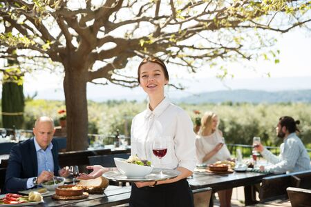 Positive woman waiter demonstrating open-air restaurant to visitors