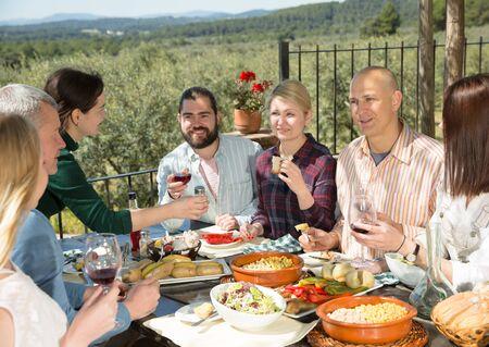 Cena de amigos al aire libre. Grupo de personas adultas felices sentados juntos en la mesa al aire libre en la casa de campo, comiendo están sonriendo Foto de archivo