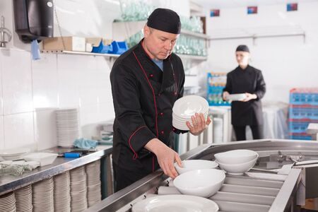 Portrait of male employee sorting and arranging clean dishware at restaurant kitchen