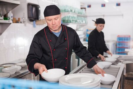 Man working in restaurant kitchen, preparing clean plates for setting on tables
