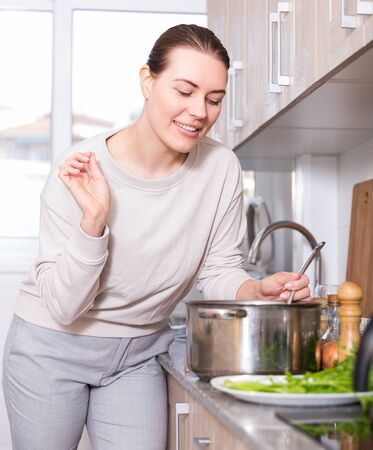 Housewife is cooking soup in pot and salt it in the kitchen at her home.