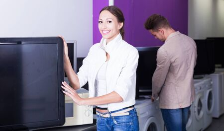 Woman purchasing flat screen television set in electronics store Banco de Imagens