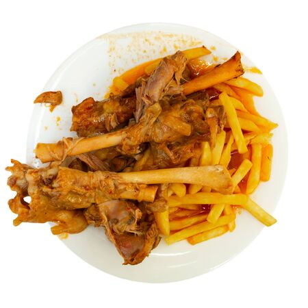 Tasty mutton meat in sauce stewed in oven served with crispy fried potatoes. Spanish cuisine. Isolated over white background
