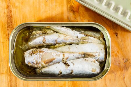 Appetizing pilchards in marinade of oil in open tin can on wooden table