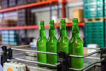 Four green glass bottles of apple cider on bottling line at factory Stock Photo