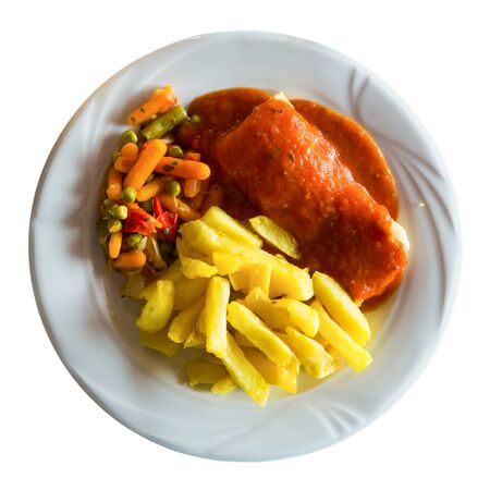 Top view of roasted cod fillet served in tomato sauce with fries and baked vegetable mix. Isolated over white background