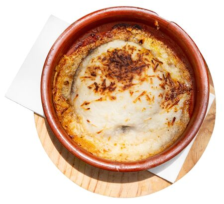 Top view of delicious Greek moussaka from baked eggplant with olive oil, meat mince and bechamel sauce served in pottery. Isolated over white background