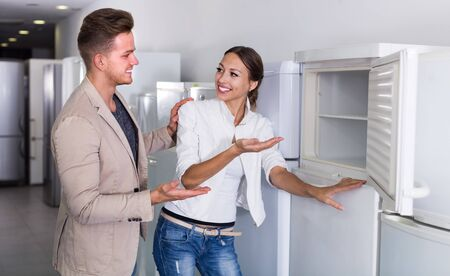Ordinary young couple selecting at fridges in domestic appliances store