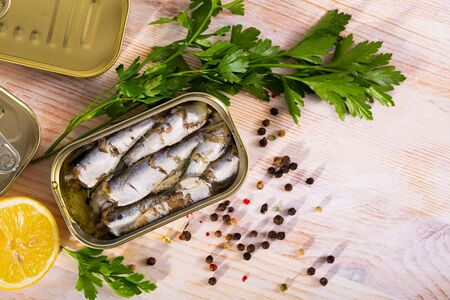 Open tin can of sprats, sardines in marinade of oil on wooden tabble