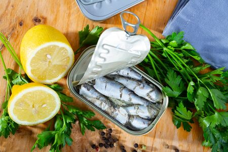Canned sea fish, sardines in oil served with herbs and lemon