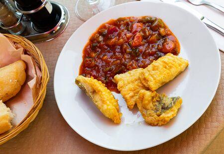 In bloem gebakken kabeljauw geserveerd met ratatouille – Spaans visgerecht Stockfoto