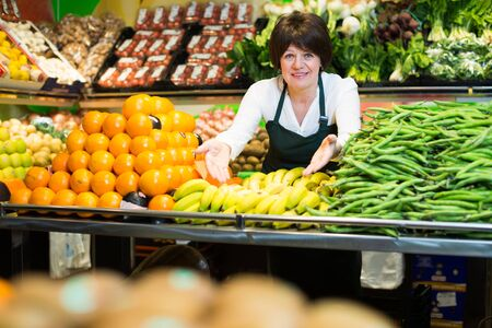 Portrait of adult female selling fruits and vegetables on the store