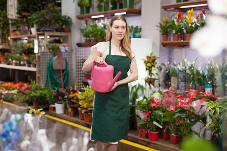 Woman florist working in floral shop; watering flowers from a plastic watering can