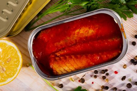 Open can of mackerel fillets in tomato sauce on wooden table Stock Photo