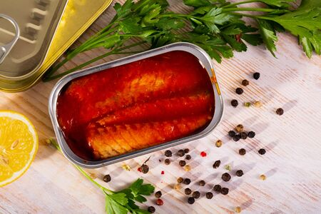Canned sea fish, mackerel fillets in tomato served with herbs and lemon on wooden table