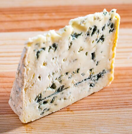 Image of slices of blue cheese with mold at plate, nobody