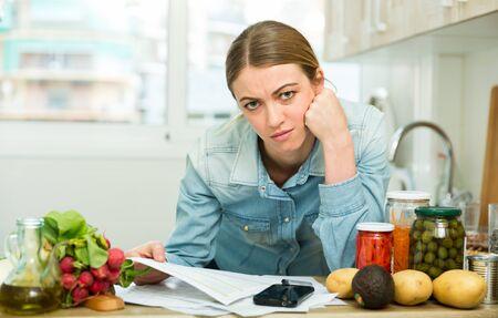 Porträt einer Frau, die in der Küche mit Papieren arbeitet, besorgt über Schulden auf Rechnungen