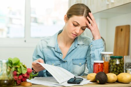 Young pensive housewife calculating family budget at kitchen