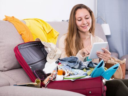 Smiling woman sitting on sofa and packing suitcase at home