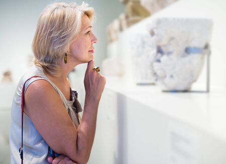 Portrait of positive senior female visitor in the historical museum looking at exhibit