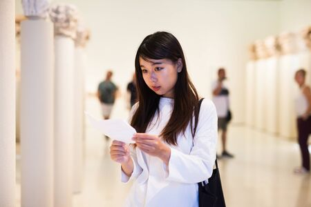 Portrait of young chinese woman with guide looking at exhibition in museum of arts