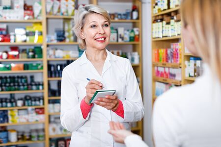 Glad cheerful positive smiling mature female seller suggesting care products to young customer in specialized shop